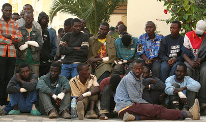 Would-be immigrants sit in a police station in Spain's North African enclave of Melilla