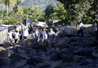 Residents search for survivors among rocks on a damaged road after heavy rains brought on by Hurricane Ida, in the village of Verapaz