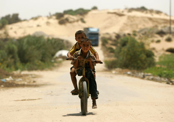Two Palestinian Bedouin brothers ride bicycle back home near the Jewish settlement of Gush Katif.