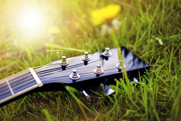 Detail of acoustic guitar on a grass. Natural background with flowers, grass and sun. Musical instrument.