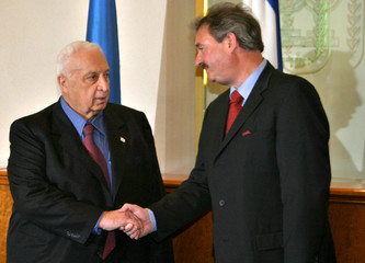Israeli Prime Minister Ariel Sharon shake hands with Luxembourg's Foreign Minister Jean Asselborn ...