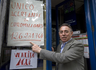 Lottery kiosk employee points to sign of record lottery ticket sold in Madrid