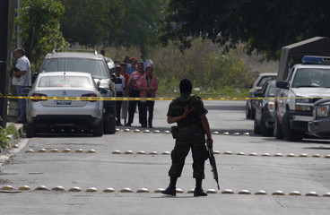 Soldier guards a crime scene where the bodies of three people were found at an abandoned warehouse in Monterrey
