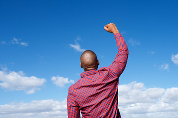 back of man with arm raised in the air