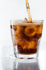 stream of cola is poured into a glass with ice