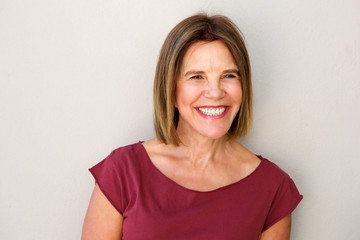 Close up beautiful middle age woman smiling against white wall