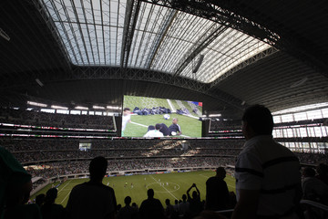 Fans are silhouetted against dual video screens hanging above field at the Cowboys Stadium in Arlington