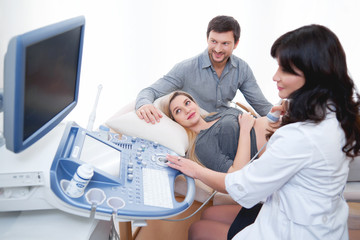 Professional gynecologist using ultrasound scanning machine during examination of her pregnant patient technology modern medicine occupation job trust pregnancy family couples healthcare love.