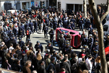 Riot policemen surround a car after the driver knocked down some students in Paris