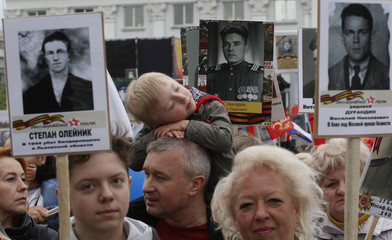 People carry pictures of World War Two soldiers as they take part in Immortal Regiment march during Victory Day celebrations, marking tWorld War II anniversary, in rebel-held Luhansk