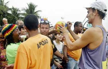 Emanuel of Brazil signs autograph after winning his beach volleyball match against Argentina in Rio ...