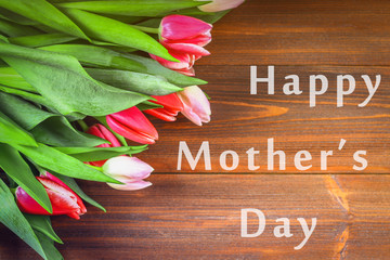 happy mother's day text sign on pink tulips on white rustic wooden background. greeting card concept. sensual tender women image. spring flowers flat lay