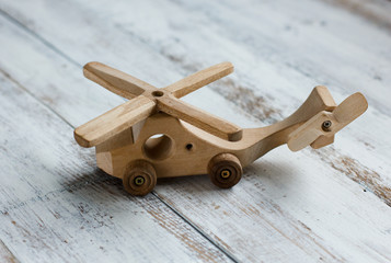 Simple wooden helicopter toy on white old table background. Best present for children