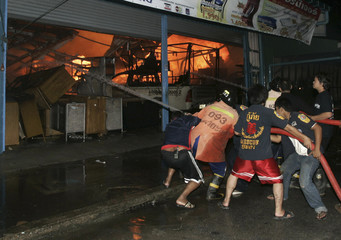 People work to extinguish a fire at the site of a bomb blast in Thailand's Yala province