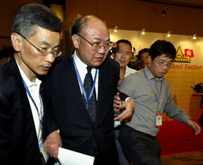 Electoral chairman Justice Woo Kwok-hing is chased after by reporter at the ballot counting centre in ...