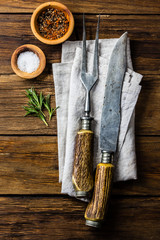 Carving set cutlery, spices and rosemary on wooden background