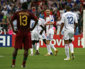 France's Zinedine Zidane (2nd R) celebrates with team mates after scoring their first goal as Portug..