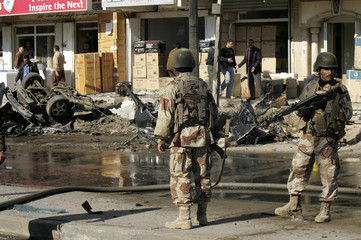 Iraqi soldiers patrol a road near destroyed cars in Baghdad