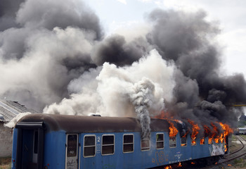 A crashed train carriage engulfed by fire is seen during a simulated disaster relief exercise in Budapest