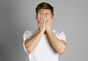 Man in white t-shirt covering his face with hands over gray background