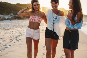 Stylish young women walking on a beach