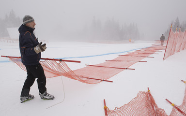Course workers remove security fences after the men's Alpine Skiing World Cup Downhill was cancelled due to fog and poor visibility in Garmisch-Partenkirchen
