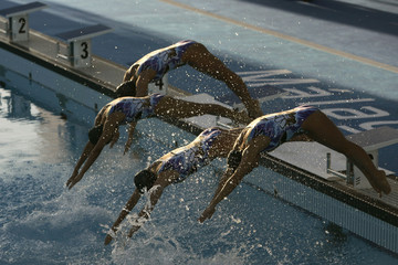 Spain's synchronized swimming team dive into the water during an exhibition in Malaga