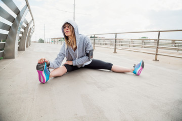 Young woman doing stretching on a modern bridge after intensive sports training. She is blonde, wearing hoodie and listening music