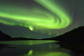 The Aurora in the sky above the hills . Reflected in the lake.
