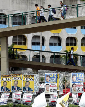CAMPAIGN POSTERS CLUTTER OVERPASS WALL NEAR A SHANTYTOWN IN RIO DEJANEIRO.