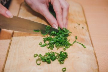 To cut green onions. The girl cuts green onions on a wooden board.