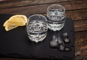 Gin tonic, vodka or rum with ice and lemon on slate board on wooden background.