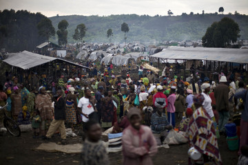 People displaced by war gather at a market in the middle of a camp in eastern Congo