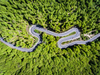 Winding road in the forest. Transylvania, Romania, Europe. Truck passing on road.