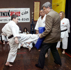 Stephen Harper holds a pad as student of Burtnik Karate demonstrates his kick in St Catharines