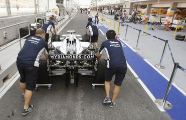 The car of Williams Formula One driver Kazuki Nakajima of Japan is pushed to be scrutinised as preparations are made for the Singapore F1 Grand Prix