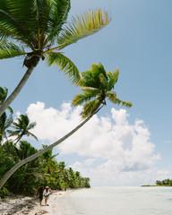 Couple walking along beach, rear view, Tahiti, South Pacific