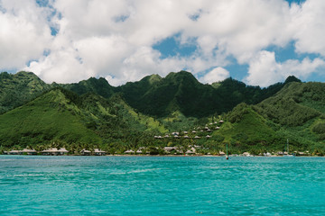 Green mountains, sea, cloudy sky and bungalows, Tahiti, South Pacific
