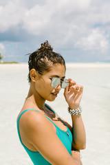 Portrait of woman at beach, wearing swimwear and sunglasses, Tahiti, South Pacific