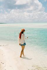 Woman walking along beach, looking at view, Tahiti, South Pacific