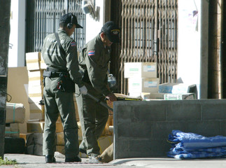 TWO THAI BOMB SQUAD EXPERTS EXAMINE SUSPECTED OBJECTS.