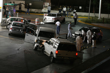 Forensic workers inspect a crime scene after a shooting in a wealthy neighbourhood of Monterrey