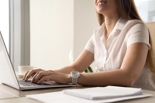 Close up photo of womans hands typing on laptop. Smiling woman working on computer. Female office worker doing daily routine. Workplace ergonomics and correct posture, tunnel syndrome prevention