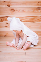 baby boy with brown eyes is five months old wrapped in a white towel with ears on wooden background .