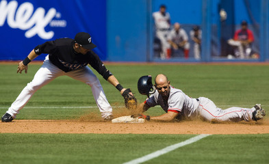 Boston Red Sox Alex Cora is safe at second base after hitting a double against the Toronto Blue Jays in Toronto