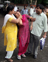 Relatives console woman mourning the death of husband who was killed in a bomb blast in train  in Mumbai