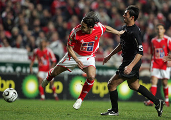 Benfica's Gomes is tackled by Academica's Serraro during their Portuguese Premier League match in Lisbon