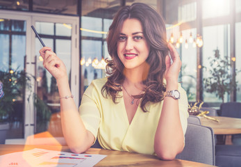 Portrait of young beautiful businesswoman sitting at table in restaurant.