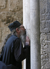 An Orthodox priest kisses a column before he enters the Church of the Holy Sepulcher in Jerusalem's Old City