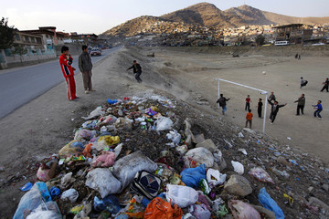 Afghan boys play soccer along a road in Kabul
